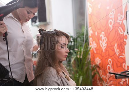 Side view of beautiful lady in hairdressing saloon. Barber girl drying her hair by hair dryer in beauty salon.