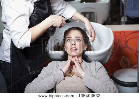 Portrair of frightened beautiful lady while having her hair wash in hairdressing salon. Pretty lady looking at camera.