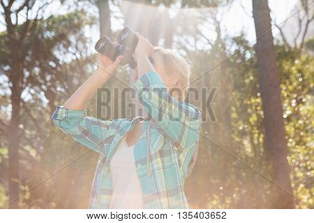 Mature woman looking on binoculars on the wood