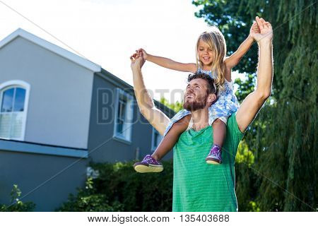 Low angle view of father carry daughter on shoulders in yard against house