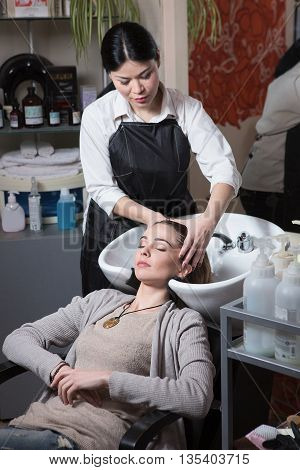 Side view of beautiful hairdresser washing hair to her client lady in hairdressing salon. Client sitting with her eyes closed.