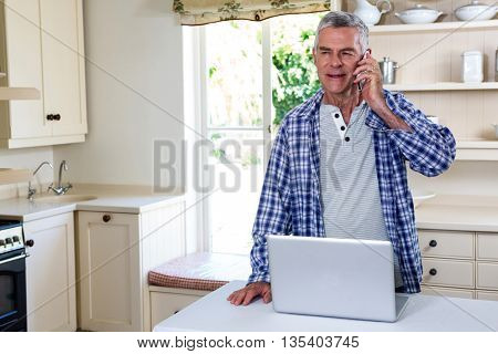 Senior man calling while standing in counter kitchen