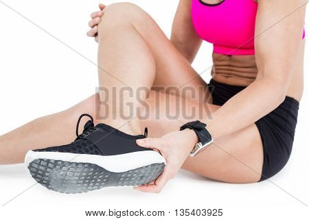 Injured female athlete sitting and removing her shoe on white background