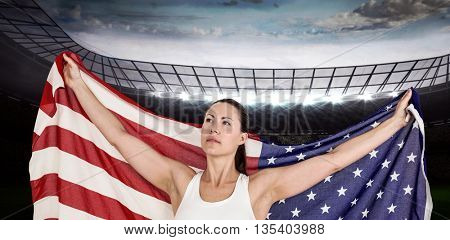Female athlete posing with american flag against rugby stadium