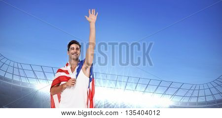 Athlete with american flag wrapped around his body against large football stadium under bright blue sky