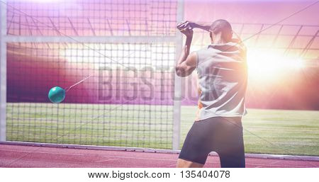 Rear view of sportsman practising hammer throw against race track