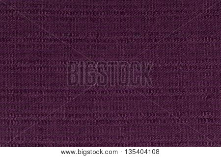 Dark burgundy purple background from a textile material. Fabric with natural texture. Cloth backdrop.