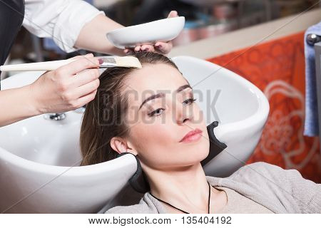 Barber girl combing her hair in beauty salon. Beautiful lady having her hair washed by hairdresser in hairdressing salon.