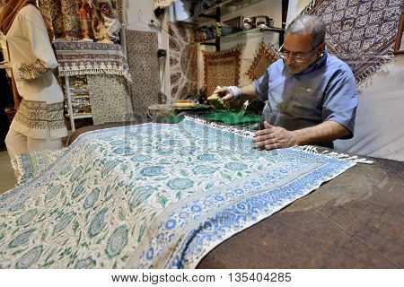 ISFAHAN - APRIL 18: Unknown man making traditional iranian souvenirs in a market (Isfahan Bazaar) in Isfahan, Iran on April 18, 2015. Bazaar is the most important tourist attraction in Isfahan, Iran.
