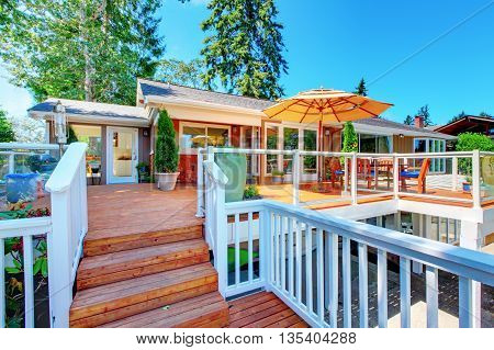 Cozy Screened Walkout Deck With Patio Area And White Railings Staircase.