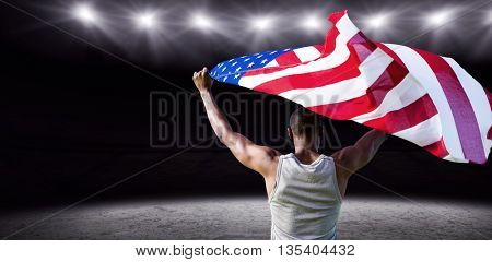 Rear view of athletic man holding the American flag against rugby stadium