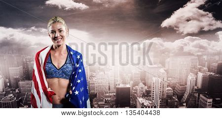 Athlete with american flag wrapped around her body against aerial view of a city on a cloudy day