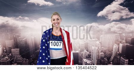 Athlete with american flag wrapped around his body against aerial view of a city on a cloudy day