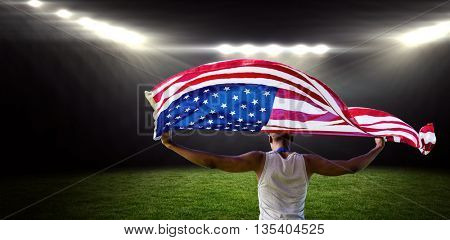 Rear view of sportsman holding american flag against rugby stadium