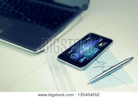 business, technology and navigation concept - close up of smartphone with gps application, laptop computer and chart with pen on office table