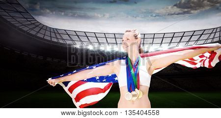 Portrait of happy sportswoman with medals holding american flag against rugby stadium