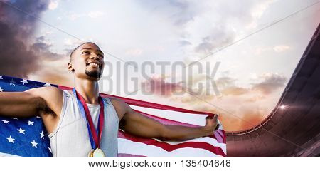 Portrait of happy sportsman posing with an american flag against composite image of stadium against cloudy sky