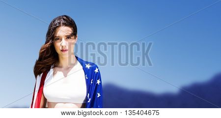 Portrait of american sportswoman is posing against scenic view of blue sky