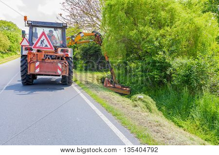 CZECH REPUBLIC, DOBRANY, 26 MAY, 2016:Tractor machine mowing grass along road.