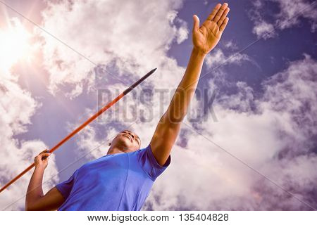 Low angle view of sportsman practising javelin throw against bright blue sky with clouds