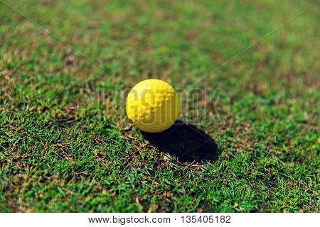game, entertainment, sport and leisure concept - close up of yellow golf ball on green field grass