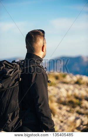 Back view of backpacker watching landscape in mountains
