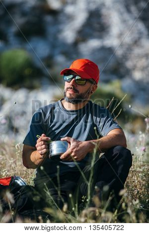 Portrait of bearded backpacker eating in sunlight from metal bowl at the mountain