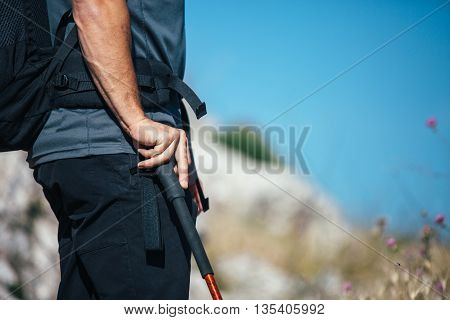Close-up of unrecognizable adult backpacker holding mountain stick against of sky. Copy space area