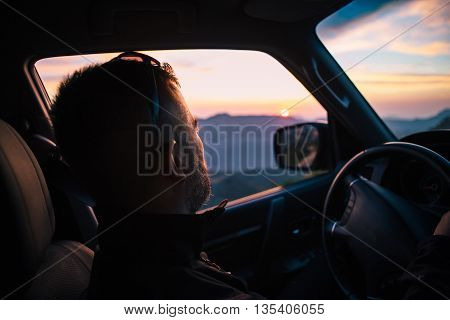 Side view of adult bearded driver steering car against of sundown in mountains