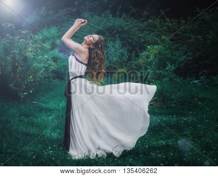 beautiful slender brown-haired young girl with long curly volosvmi in long white dress standing in the middle of a forest clearing her dress develops in the wind
