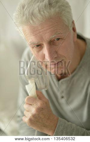 Portrait of a ill Senior man with inhaler