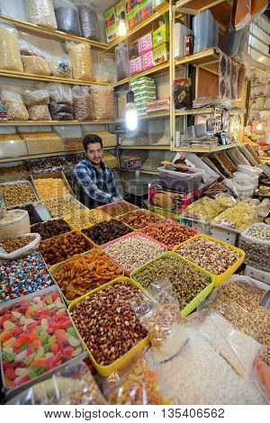 ISFAHAN - APRIL 19: Unknown man trades traditional iranian food and spices in market (Bazaar) in Isfahan Iran on April 19 2015. Bazaar is the most important tourist attraction in Isfahan Iran.