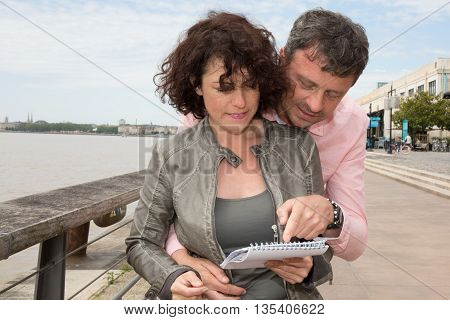 Loving Couple At The River Looking At A Guide Book