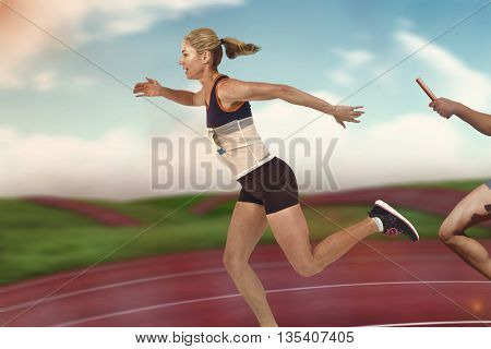 Athlete passing a baton to the partner against digital image of athletic track