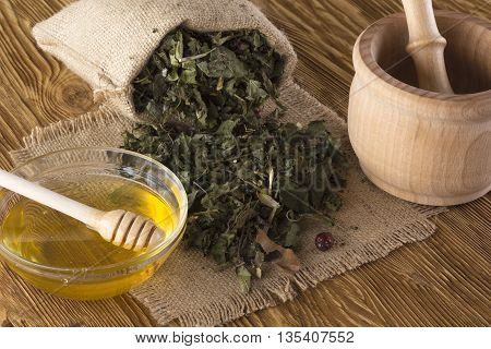mortar, pestle, honey and herbal tea on wooden table