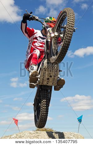 ASTON TIROLD, UK - AUGUST 8: An unnamed rider reaches the top of a steep slab and ditch section at the NBMCC Supertrial event held at Seymours arena on August 8, 2015 in Aston Tirold