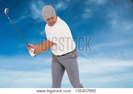 Golf player taking a shot against blue sky