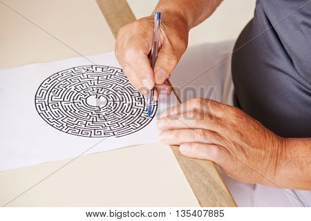 Old man doing memory training with paper maze in a nursing home