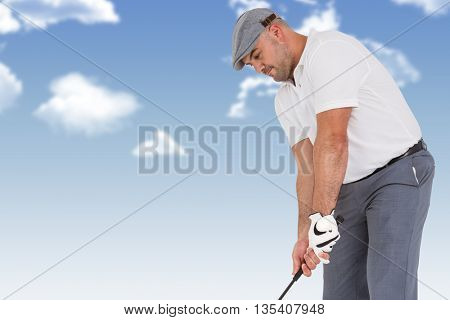 Golfplayer about to swing a golf ball against blue sky