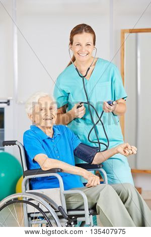 Smiling nurse measuring blood pressure of old woman in a wheelchair