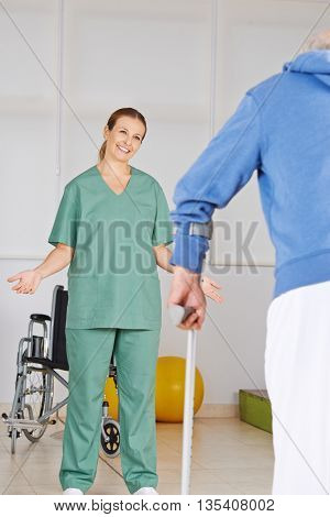 Smiling physiotherapist motivating old man with crutches to walk