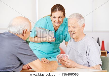 Smiling geriatric nurse watching twi old men playying cards in a nursing home