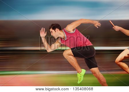 Confident male athlete running from starting blocks against digital image of an athletic track