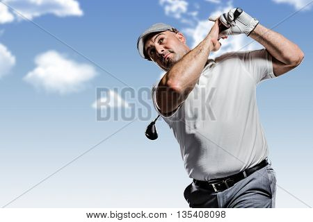 Portrait of golf player taking a shot against blue sky