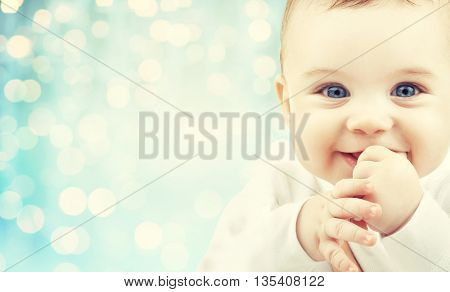 babyhood, childhood and people concept - happy baby face over blue holidays lights background