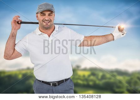 Portrait of golf player holding a golf club against country scene