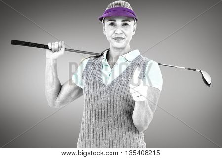 Pretty blonde playing golf and showing a thumbs up against grey vignette