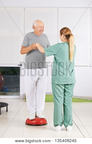 Old man exercising with physiotherapist in physiotherapy