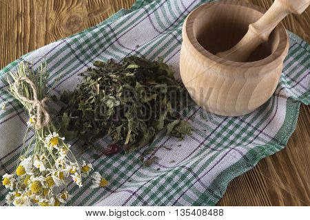 mortar and pestle with herbal tea on wooden background.