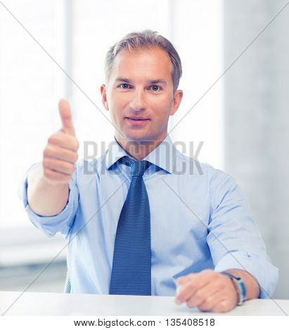 picture of smiling businessman showing thumbs up